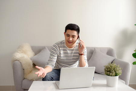 Asian young man working at home with smartphone and laptop on sofa. 스톡 콘텐츠