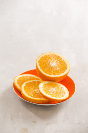slices of oranges in white dish on dark wooden table. Stock Photo