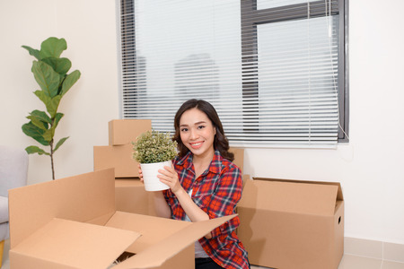 Excited young asian woman unpacking carton boxes with cozy home stuff in new apartment. Foto de archivo - 109356334