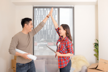 Asian young couple plan interior of new house. They read blueprint near many moving cardboard boxes. Design of decoration at wall and ceiling. First buying home to start family life . Archivio Fotografico - 109356339