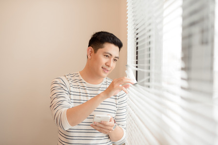 Young cheerful man holding on phone while leaning against windowsill Stock Photo