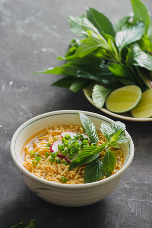 Instant noodles in bowl with fresh herbs, garnish of cilantro and Asian basil, lemon, lime on dark stone background