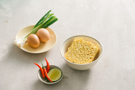 Instant noodles in bowl and vegetable side dishes on stone background. Quick & easy food concept. Stock Photo