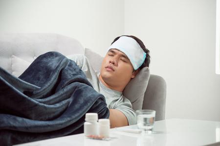 kranker verschwendeter Mann, der im Sofa liegt, das unter Erkältung und Wintergrippevirus leidet, das Medizin-Tabletten im Gesundheitskonzept sieht, das Temperatur auf Thermometer schaut Standard-Bild