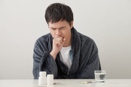 Sick man lying on bed and coughing a lot
