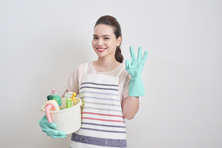 Young woman as a cleaning maid holding bucket full of liquids and showing OK sign, isolated over white Stock Photo