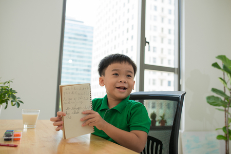 Head shot Portrait of happy asian cute child doing homework with smile face at home .