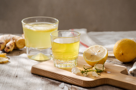 Refreshing summer drink with lemon, ginger, rosemary and ice on rustic wooden table, copy space