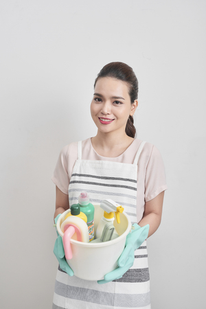 people, housework and housekeeping concept - happy woman holding cleaning stuff at home Фото со стока