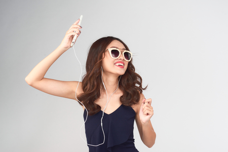 Happy carefree young woman dancing and listening to music from smartphone over grey background Stockfoto