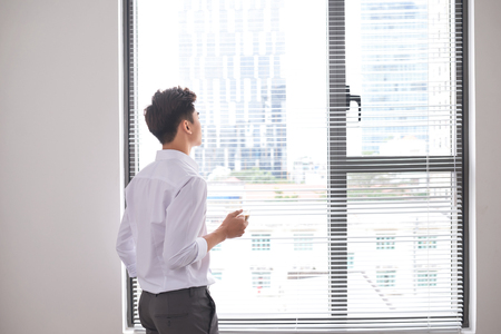 Portrait of a confident young businessman holding a cup of coffee while standing near office window, intelligent men in white shirt while resting after meeting Stockfoto
