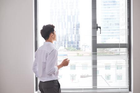 Ritratto di un giovane uomo d'affari fiducioso che tiene una tazza di caffè mentre si trova vicino alla finestra dell'ufficio, uomini intelligenti in camicia bianca mentre riposano dopo l'incontro Archivio Fotografico
