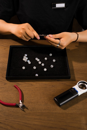 Hands of female jewelry designer looking at her work with magnifying glass