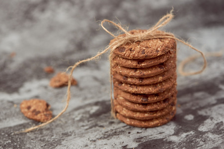Chocolate chip cookies are stack and tied with twine on stone background