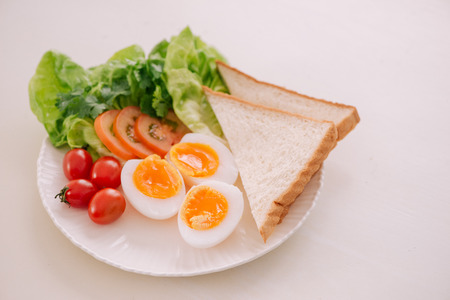 Fresh garden salad with egg, avocado and tomato in brownstone dish for a healthy low calorie lunch. Фото со стока