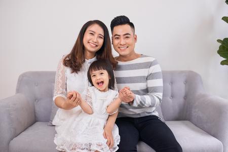 Aufnahme eines lachenden kleinen Mädchens, das morgens mit ihren Eltern auf der Couch sitzt. Standard-Bild