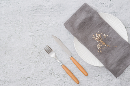 Table prepared for reservation. Arranged fork, knife and plate along with a towel in a restaurant Stock Photo