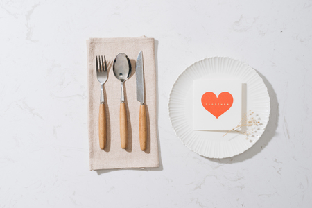 love dinner setting fork and spoon tie with red ribbon on plate on white background , love and romance concept