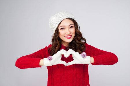 Beautiful smiling woman in warm clothing gesture heart shape Standard-Bild