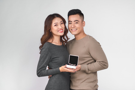 Asian man gives jewelry in a box to his woman