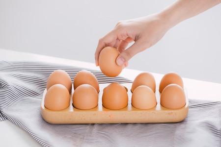 cueillir à la main un œuf dans un plateau à œufs.