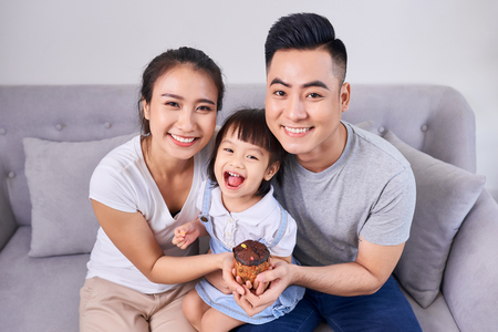 Lively family eating cupcakes in the living room at home 写真素材
