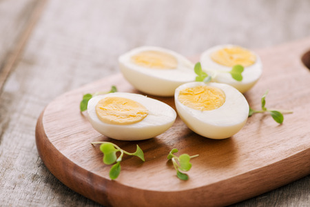 Huevos duros en tabla de cortar. Enfoque selectivo, espacio para texto