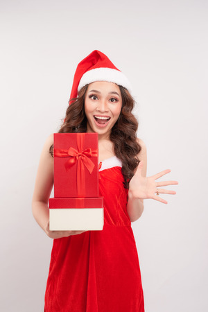 Portrait of a lovely girl dressed in christmas hat holding present boxes and looking away isolated over white background Stock Photo