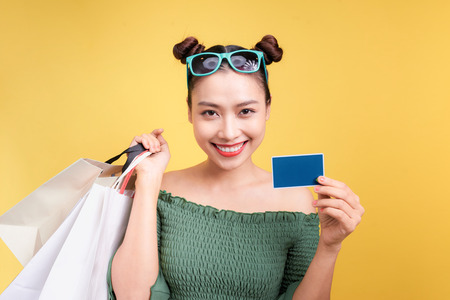 Shopping asian woman holds shopping bags and a credit card on yellow background Imagens