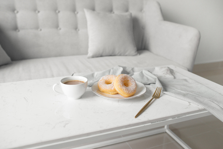 Classic donut. Morning breakfast on table in living room at home.