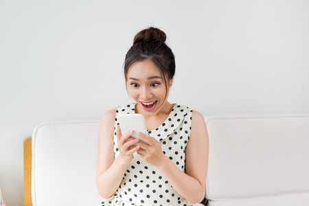 Young asian woman sitting on couch at home and using smartphone. Archivio Fotografico