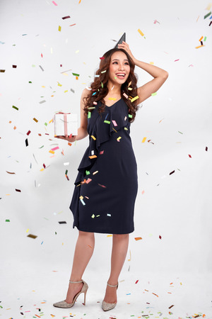 Beautiful happy woman with gift box at celebration party with confetti falling everywhere on her. Birthday or New Year eve celebrating concept Stock fotó - 111090485