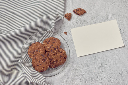 Chocolate chip cookies on plate with blank message card on white stone background Stock Photo