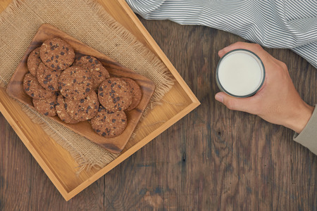 Top view -  chocolate chip cookies on plate and hand holding glass of milk on a wood table