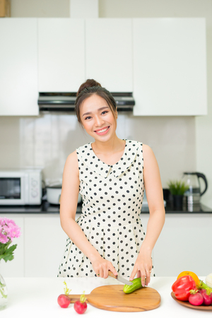 Portrait of young asian beautiful woman cooking in kitchen