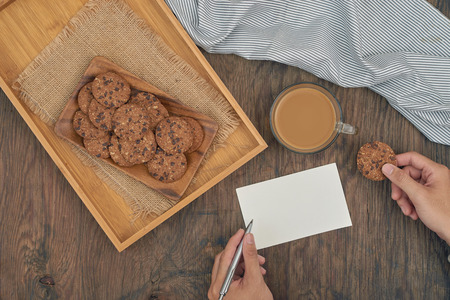 Top view -  chocolate chip cookies on plate, glass of milk and writing message on a wood table Standard-Bild - 111094148