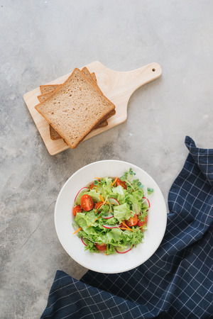 delicious autumn vitamins vegetarian salad: radish, spinach, lettuce, cress on white dish with toast on old dark rustic table, copy space left, view from above