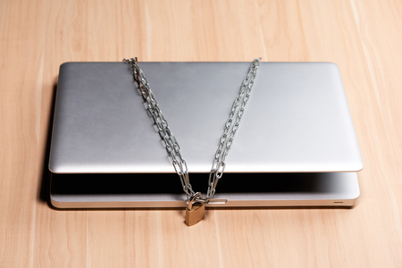 Heavy chain with a padlock around a laptop on table. Stockfoto
