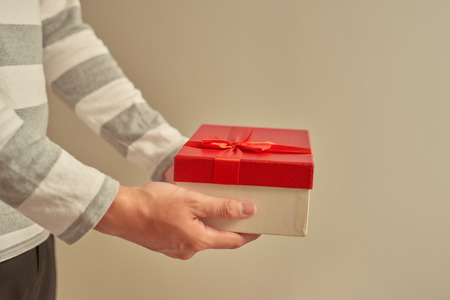 Man hand holding red gift box, male giving gift