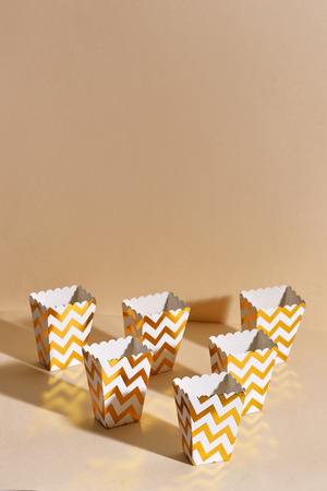 Empty paper golden Christmas cups for winter holidays meetings with friends with New Years Christmas decor on a beige background