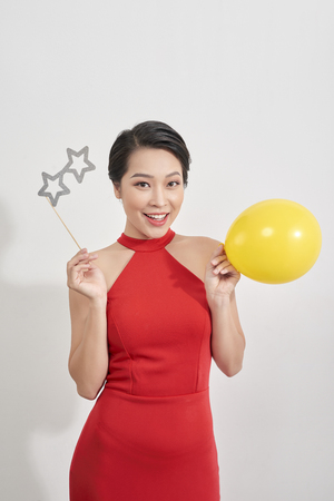 Beautiful woman in red dress is posing with paper eyeglasses in hand balloon over white background