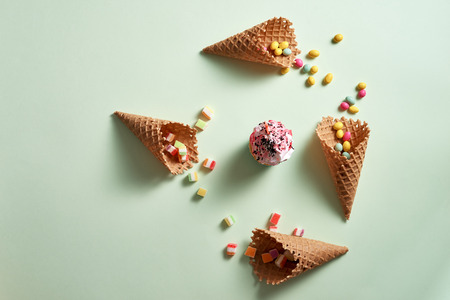 Round frame of assorted candy and waffle cones with cupcake on green background. Dessert concept. Flat lay, top view Stock Photo
