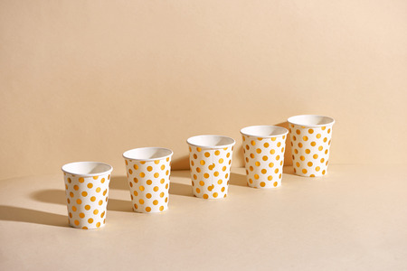 Golden polka dot paper cup isolated on beige background Banque d'images - 111112768