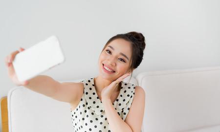 Jolie femme souriante prenant un selfie à l'aide d'un smartphone. Banque d'images