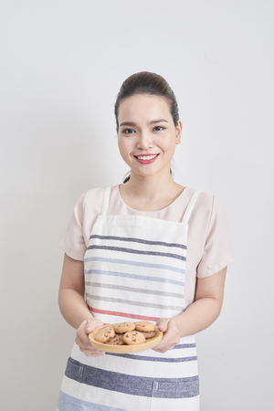 Young woman holding a plate of homemade chocolate cookies