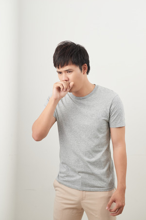 handsome man coughing into his fist, isolated on a white background Stock Photo