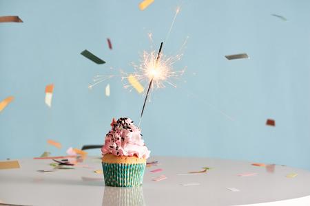 Single sparkler on cupcake blue wal Standard-Bild - 111116675