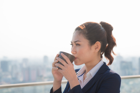 Lawyer businesswoman professional walking outdoors drinking coffee from disposable paper cup. Multiracial Asian  Caucasian businesswoman smiling