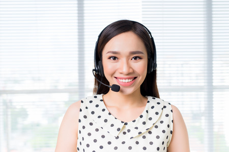 Call center operators. Young beautiful asian woman in headset Imagens