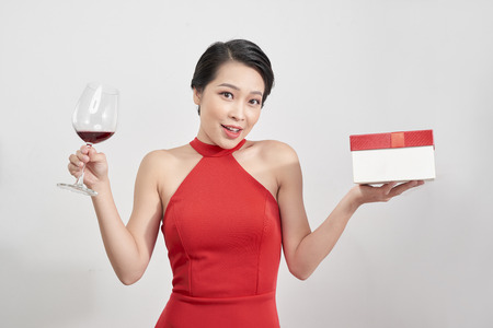 Young celebrating woman red dress . Beautiful model portrait isolated over studio background hold wine glass and christmas gift